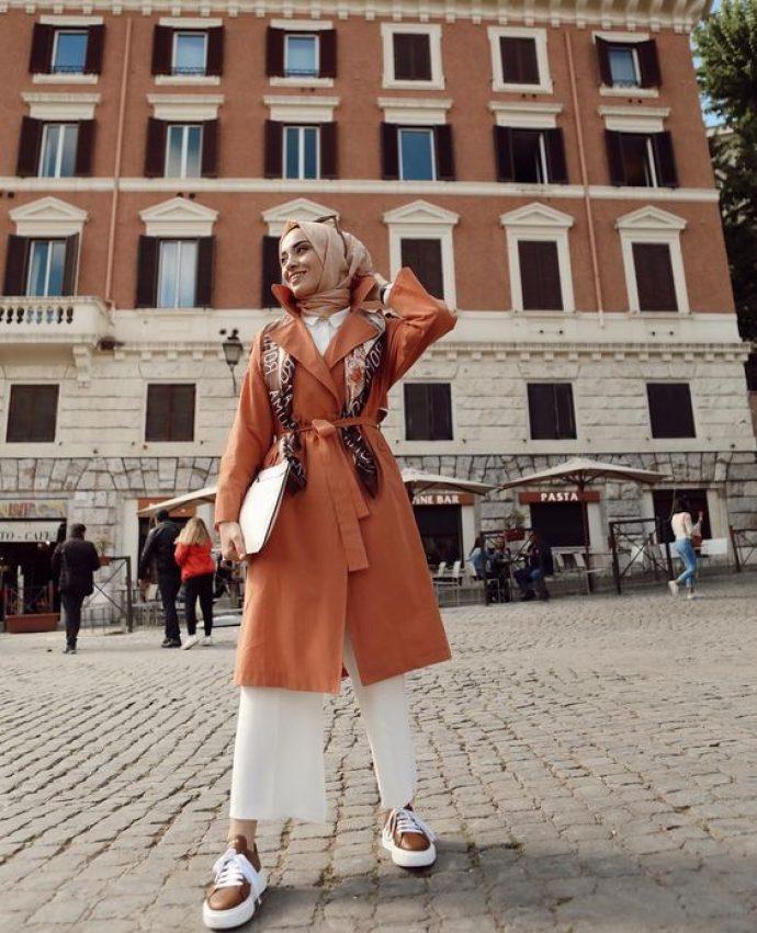 Девушка мусульманка в белых кюлотах и терракотовом пальто