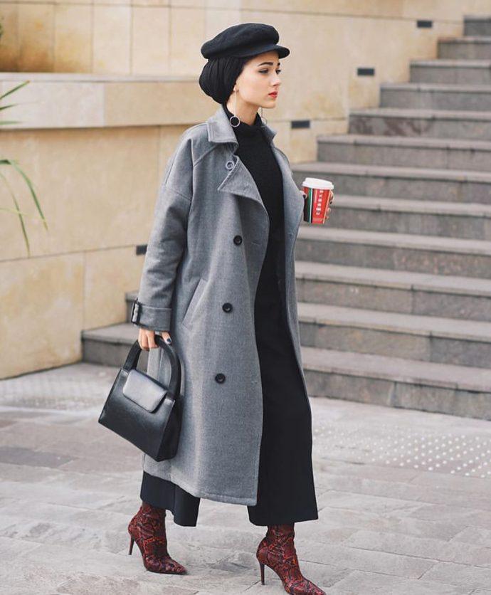 Девушка мусульманка в черных брюках, кофте и в сером пальто